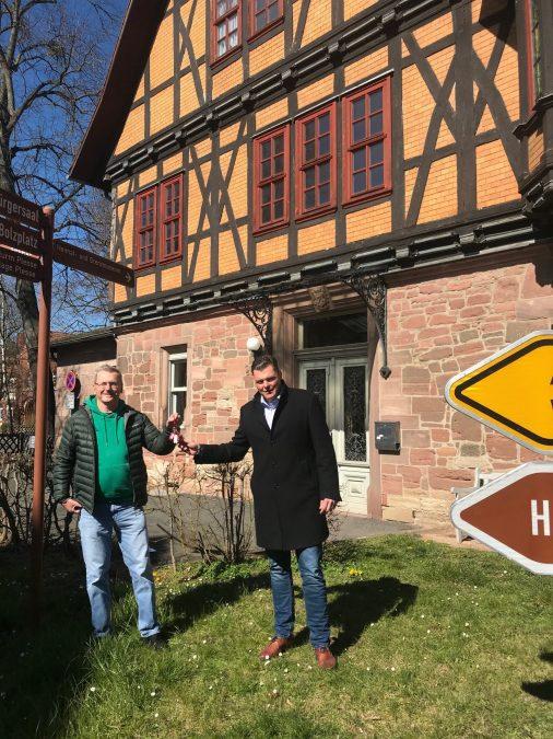 Wilfried Glembock (links) und Bürgermeister Wilhelm Gebhard (rechts) bei der Schlüsselübergabe vor dem Keudell'schen Schloss.