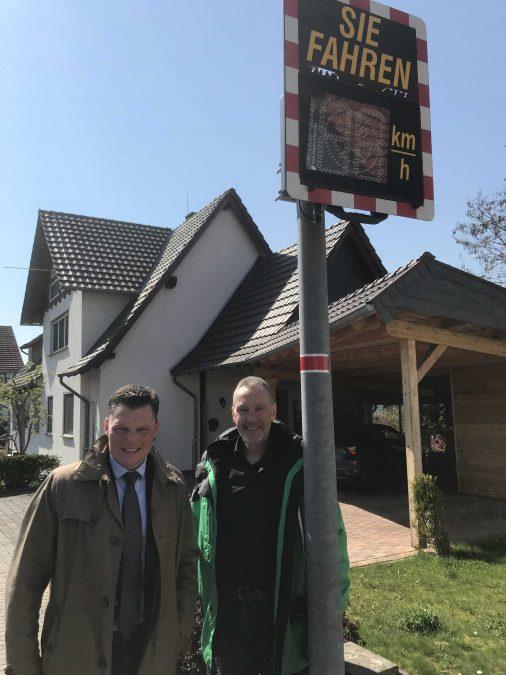 Bürgermeister Wilhelm Gebhard und Rüdiger Kunz, ehrenamtlicher Mitarbeiter der Verkehrswacht und Verkehrspolizist, vor der neu installierten Signaltafel.