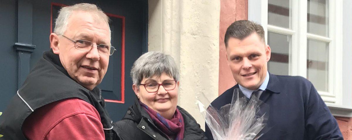 Thomas Fischbach (links) und Bürgermeister Wilhelm Gebhard (rechts) überreichen Eleonore Wehr einen Präsentkorb.