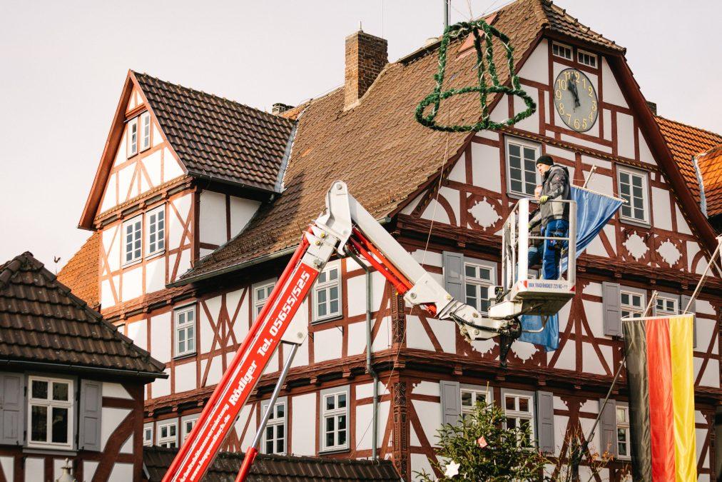 Elektromonteur Michael Stude (E-Werk Wanfried) und Wehrführer Peter Thiel (Freiwillige Feuerwehr Wanfried) in luftiger Höhe beim Montieren der beleuchteten Glocke über der Rathauskreuzung. Bild: Christoph Braun