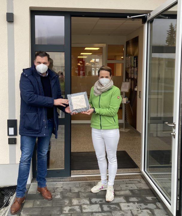Bürgermeister WIlhelm Gebhard übergibt ein Rathausrelief aus Ton an Pflegedienstleiterin Anna Sohl.